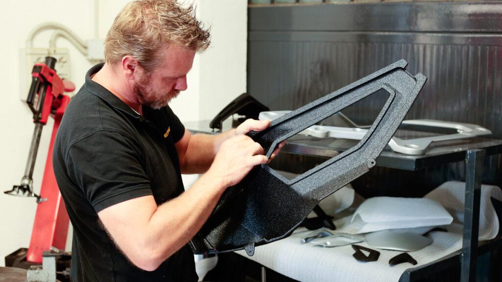 applicazione della vernice protettiva Line-x su una componente stampata 3D della moto The Rugged